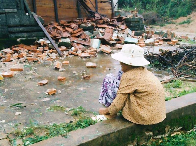 Bà cụ ngồi trông về phía căn nhà nhỏ đã bị đổ sập. Ảnh: Facebook.