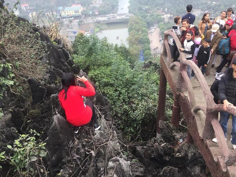 Có người còn vượt ra ngoài lan can, trèo lên các mỏm núi đá để chụp ảnh. Ảnh: Trần Quân.