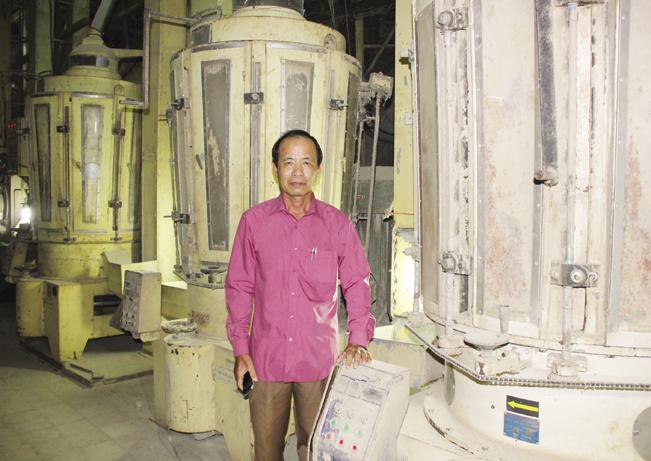 Ông Huỳnh Văn Hòa trong nhà máy xay xát lúa gạo và dây chuyền sản xuất củi trấu.