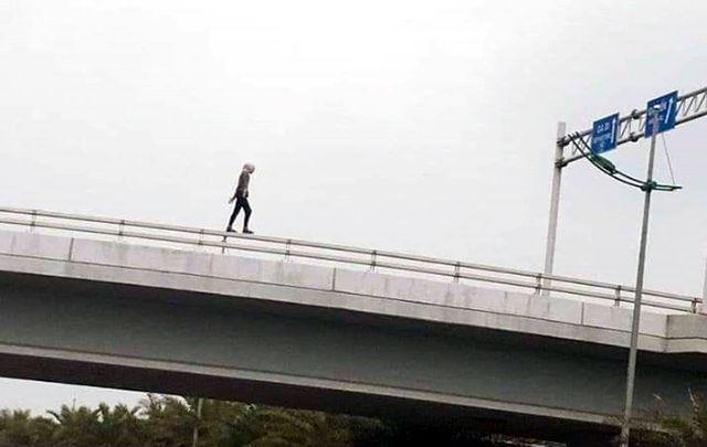 Hình ảnh cô gái đi lại trên lan can cầu vượt do người đi đường ghi lại.