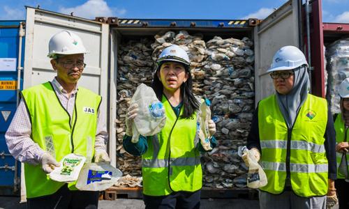 Bộ trưởng Năng lượng, Công nghệ, Khoa học, Biến đổi khí hậu và Môi trường Malaysia Yeo Bee Yin (giữa) đứng trước các container chứa rác thải nhựa tại cảng Klang. Ảnh: AFP.
