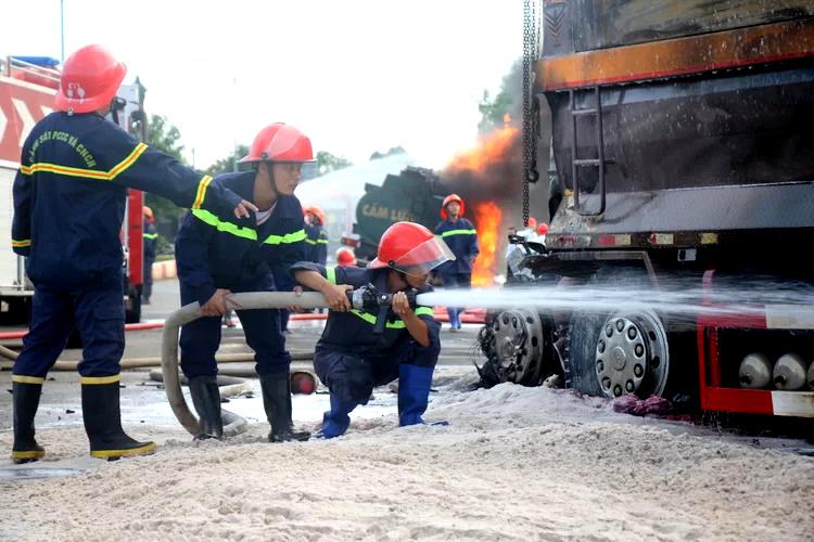 Cảnh sát chia hai tốp dập đám cháy xe bồn và liên tục phun nước dập lửa xe ben cháy âm ỉ. Ảnh: Nguyễn Khoa.
