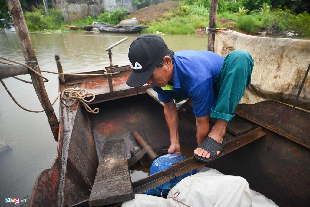 Ông Nguyễn Đinh Sưa đang gia cố thuyền của mình bằng dây thừng. Ông cho biết phải bọc lại máy thuyền và tát hết nước để tránh mưa gió quật làm đắm.