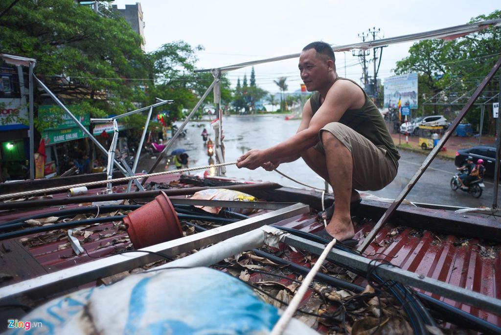 Anh Nguyễn Văn Đóa đang gia cố lại mái nhà bằng dây thừng. Các hộ dân có mái tôn đều phải dùng cách này để bảo vệ ngôi nhà của họ trước gió bão.