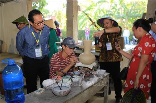 Du khách tham quan nghề làm gốm ở làng cổ Phước Tích. (Ảnh: Hồ Cầu-TTXVN)