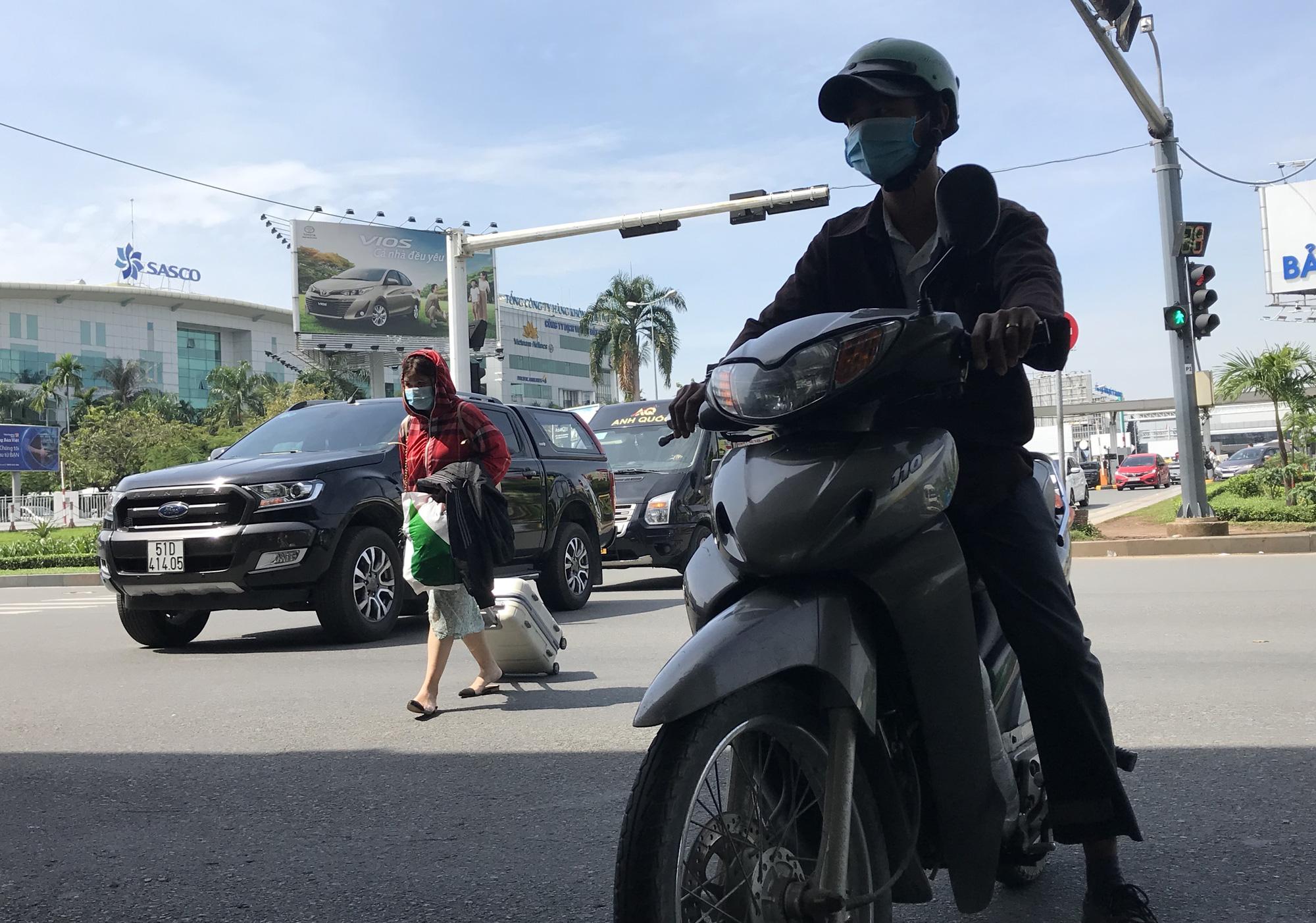 Khách vã mồ hôi, vác vali ra khỏi sân bay Tân Sơn Nhất,  cắt ngang làn ô tô để đón xe - Ảnh 4.