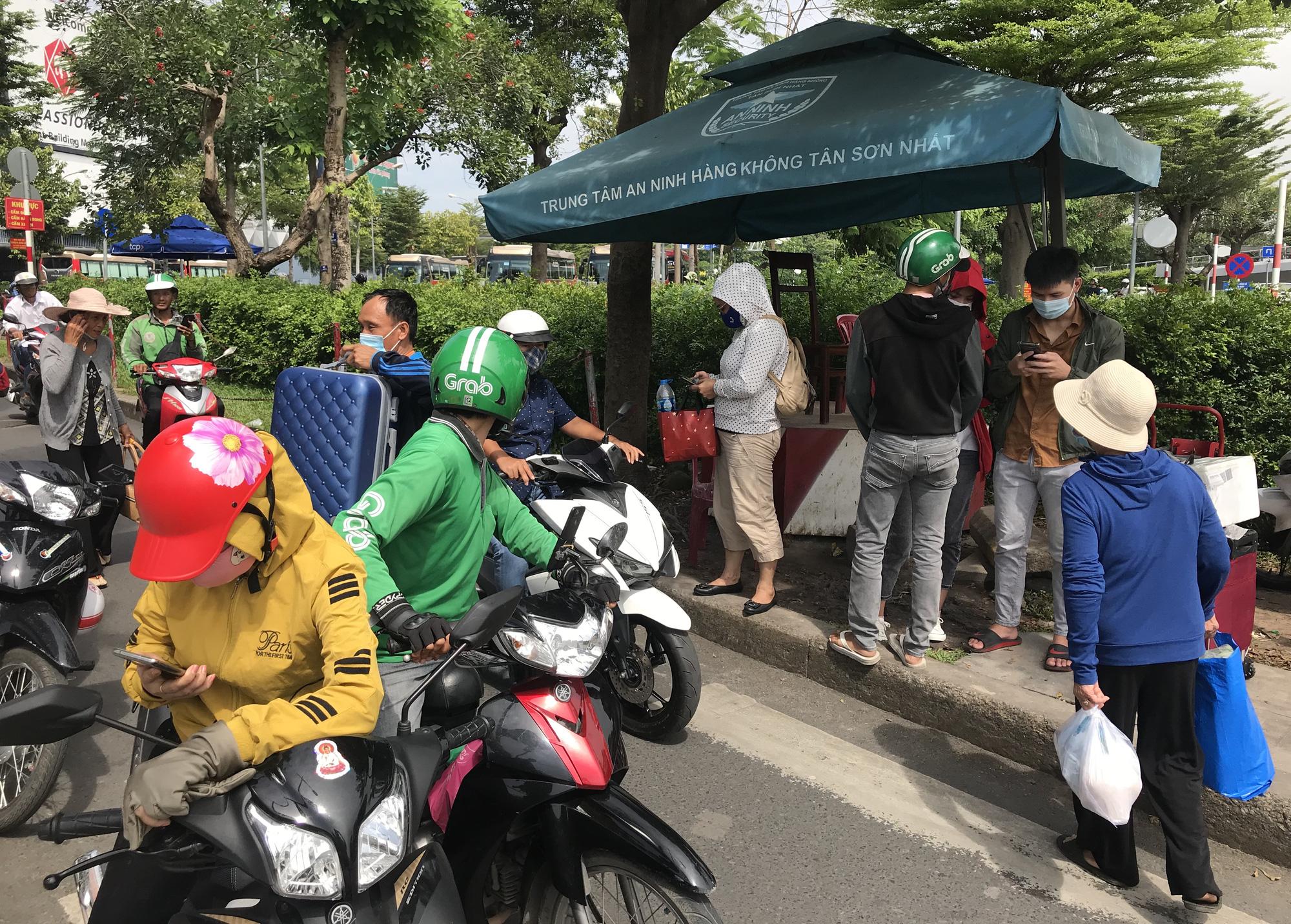 Khách vã mồ hôi, vác vali ra khỏi sân bay Tân Sơn Nhất,  cắt ngang làn ô tô để đón xe - Ảnh 5.