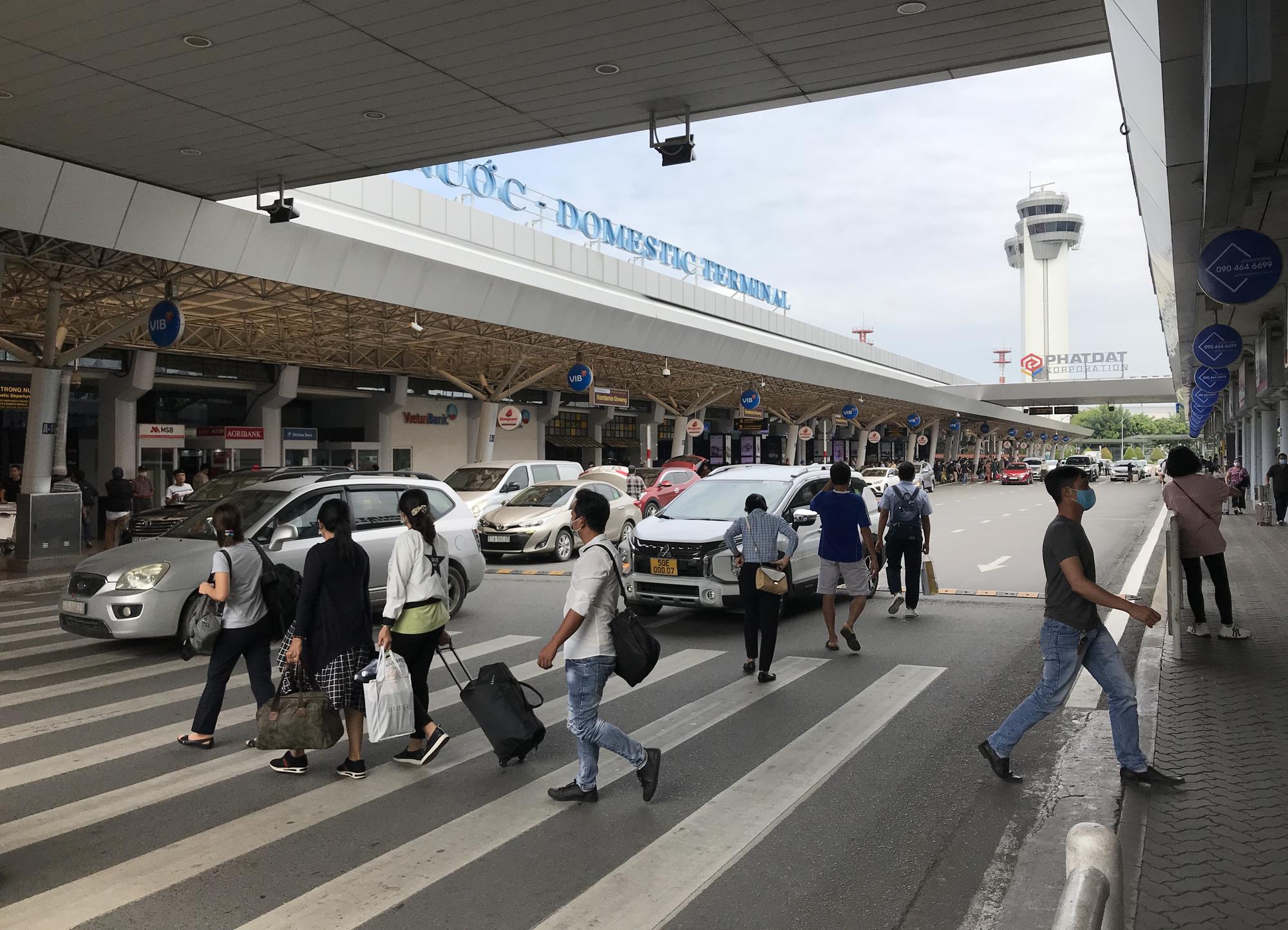 Khách vã mồ hôi, vác vali ra khỏi sân bay Tân Sơn Nhất,  cắt ngang làn ô tô để đón xe - Ảnh 7.
