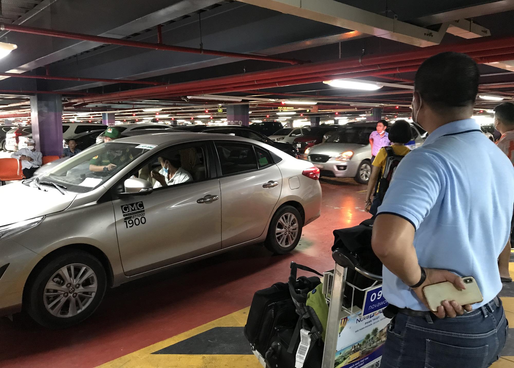 Khách vã mồ hôi, vác vali ra khỏi sân bay Tân Sơn Nhất,  cắt ngang làn ô tô để đón xe - Ảnh 9.