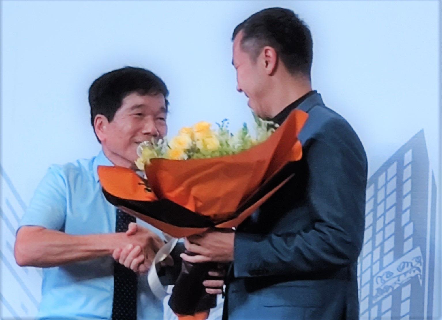 Ông Nguyễn Quốc Hiệp (trái) tặng hoa chúc mừng vị trí thành viên HĐQT nhiệm kỳ 2017 - 2021 của ông Bolat Duisenov. Ảnh: Song Minh
