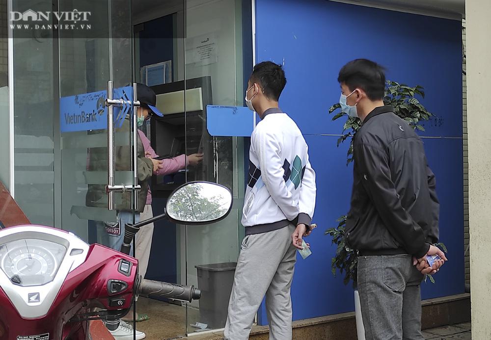 Công nhân đội mưa, xếp hàng dài rút tiền ở cây ATM ngày cận Tết Nguyên đán 2021 - Ảnh 13.