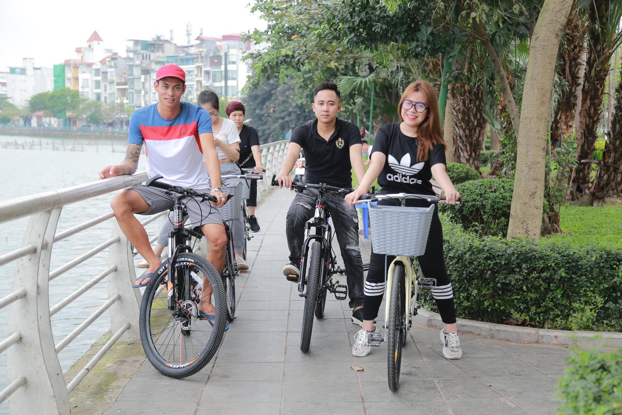 Anh Xuân Lĩnh (bên trái) tuần nào cũng thuê xe đạp xe cùng vợ và câu lạc bộ xe đạp Hồ Tây. Ảnh: N.T