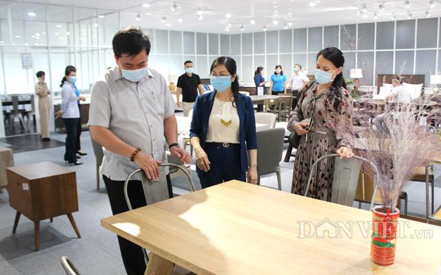 Bà Lê Thị Xuyến (giữa) giới thiệu sản phẩm gỗ nội thất cho khách hàng đến tham quan trực tiếp tại showroom