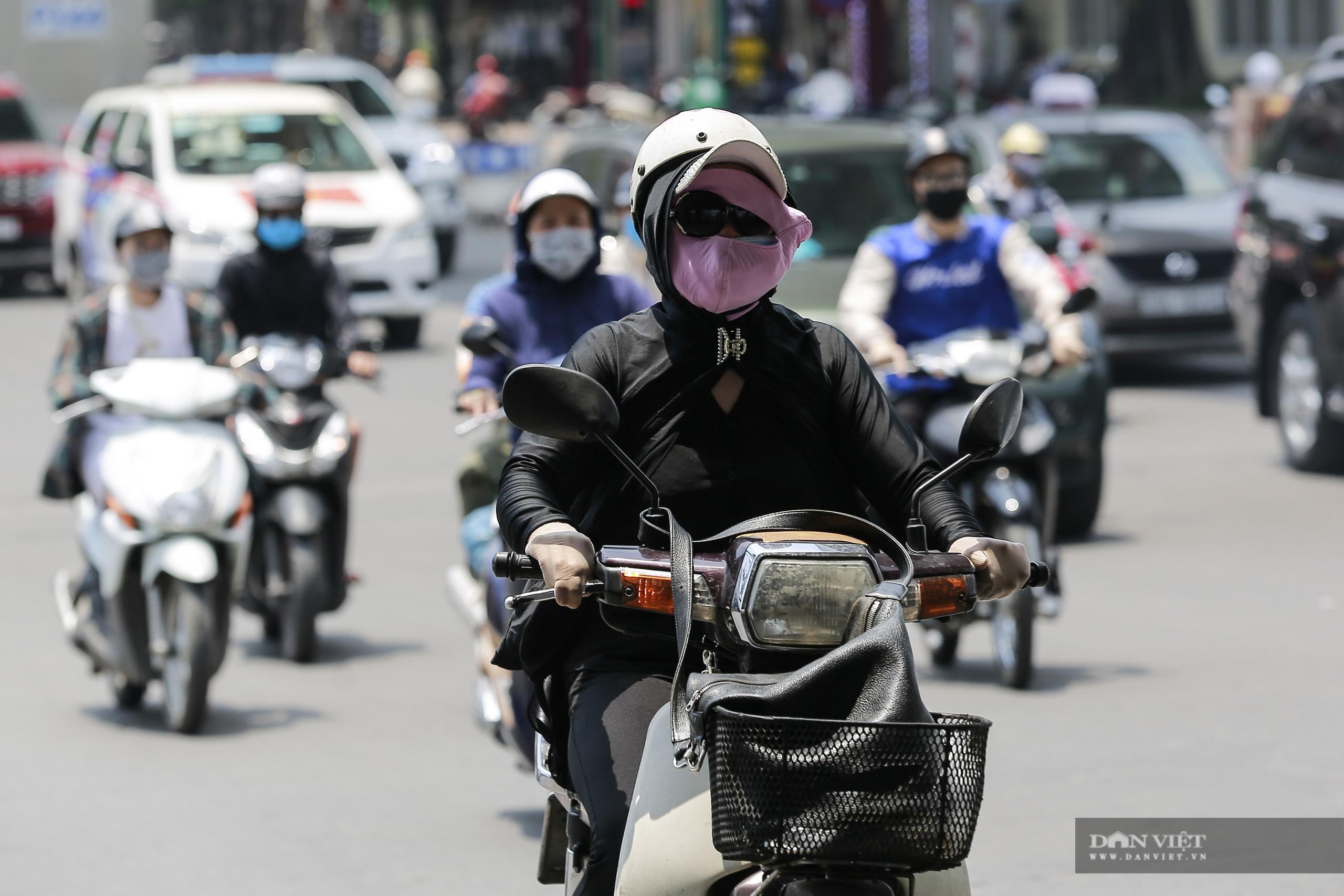Hà Nội nắng nóng gần 40 độ C, phụ nữ lái ô tô với trang phục kín mít - Ảnh 2.