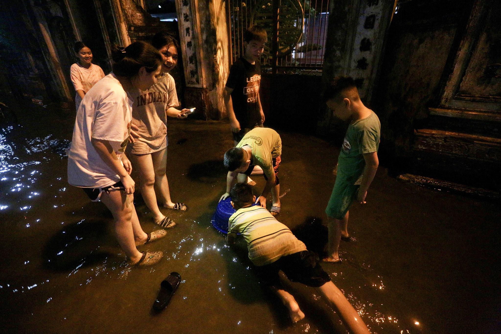 Bắt cá giữa đường sau mưa ngập ở Hà Nội - Ảnh 2.