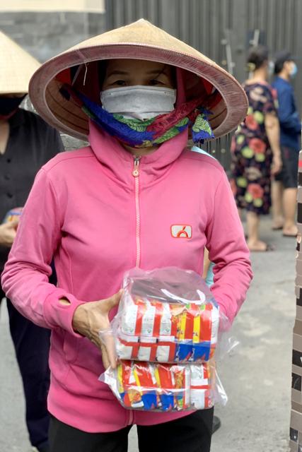 Người nghèo nhận phần quà gồm mì gói và khẩu trang