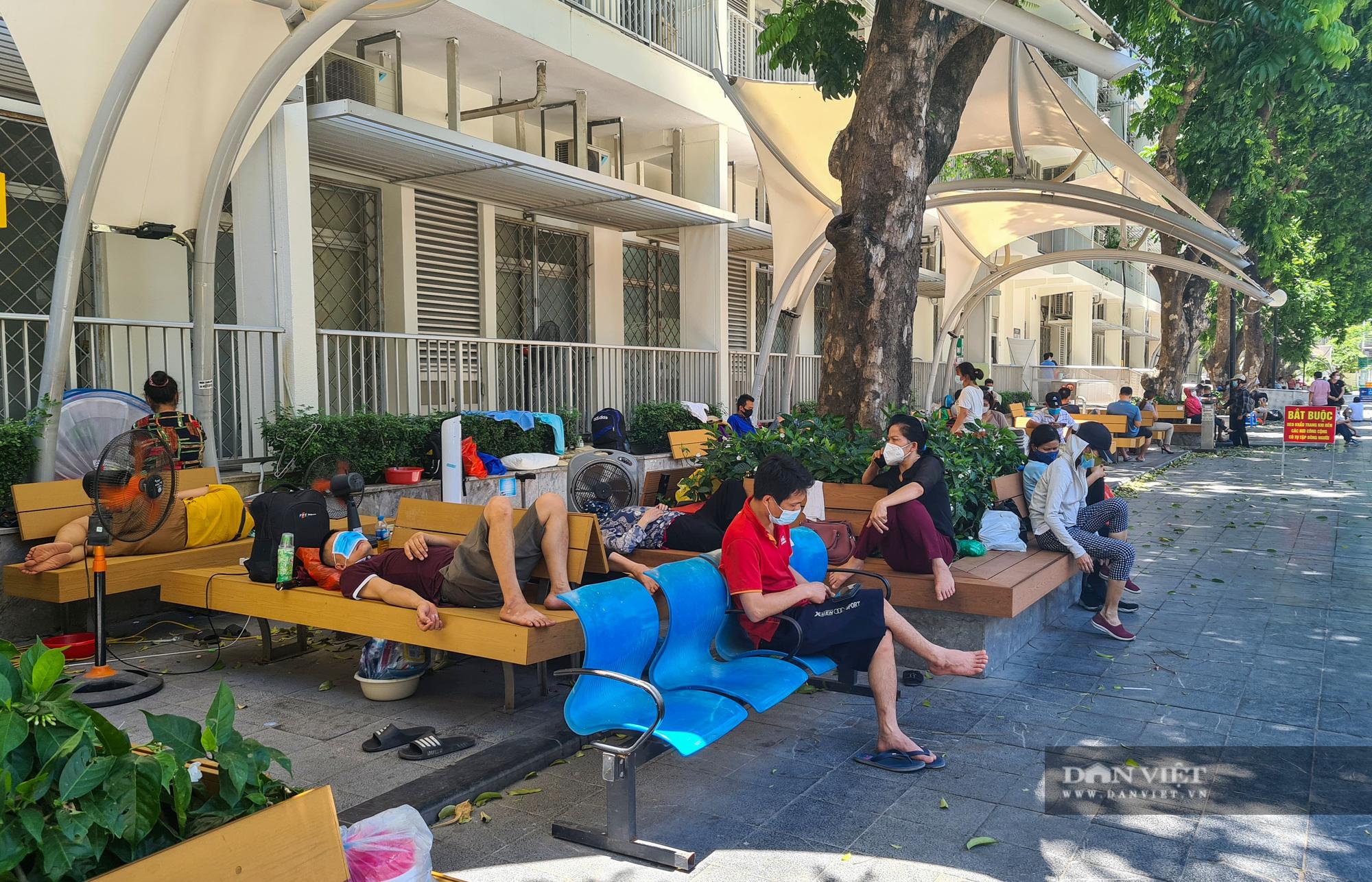 Người thân bệnh nhân tranh thủ chợp mắt giữa trưa nắng gần 50 độ tại bệnh viện Bạch Mai - Ảnh 3.