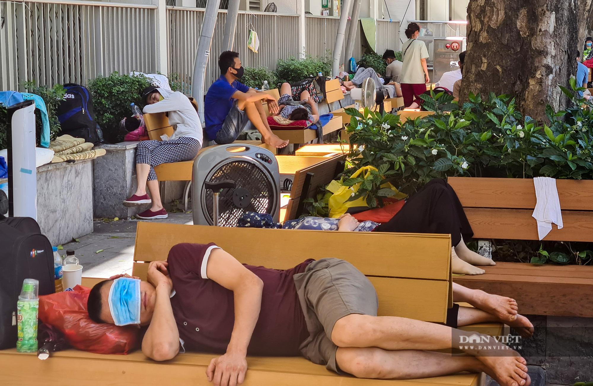 Người thân bệnh nhân tranh thủ chợp mắt giữa trưa nắng gần 50 độ tại bệnh viện Bạch Mai - Ảnh 5.