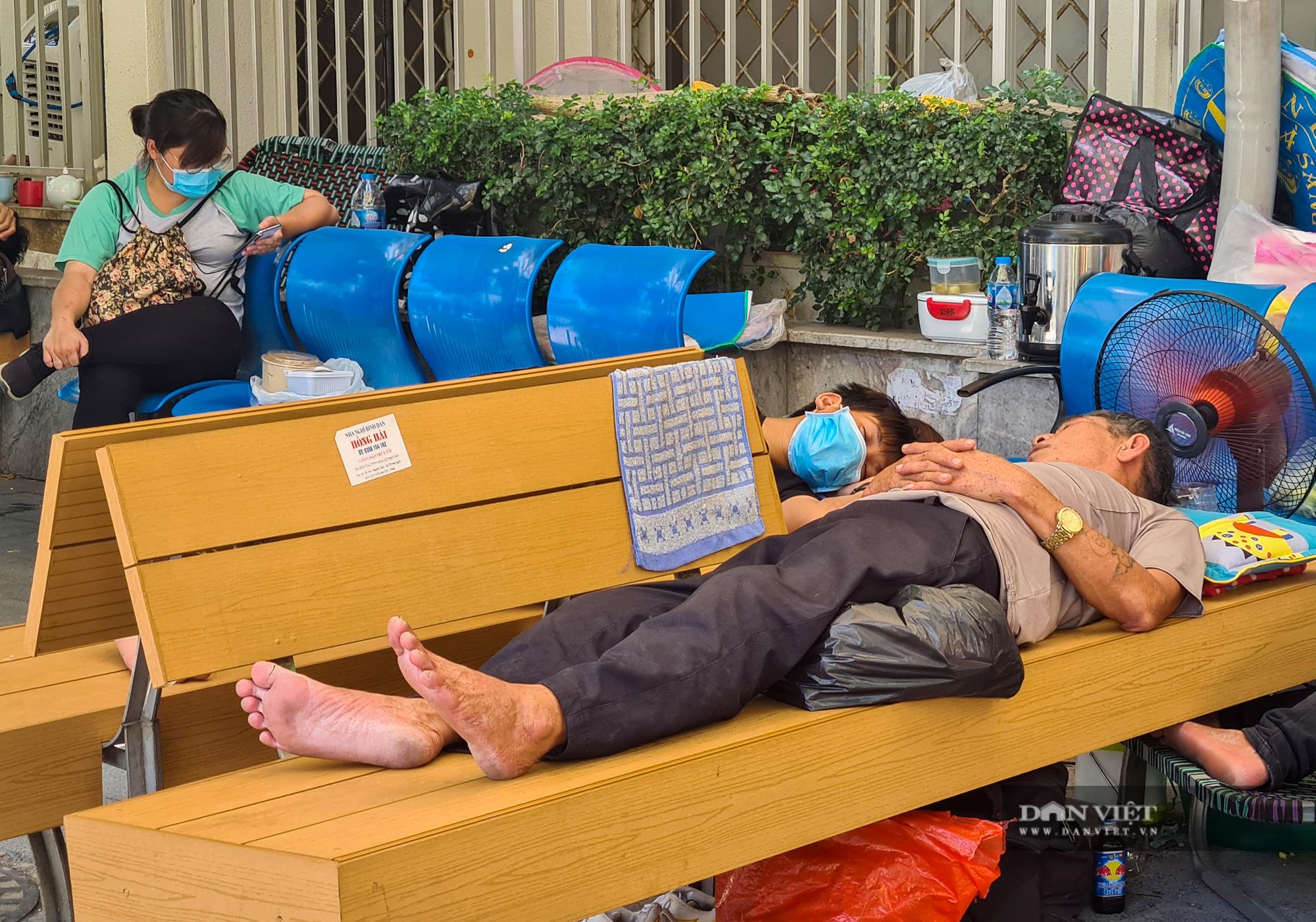 Người thân bệnh nhân tranh thủ chợp mắt giữa trưa nắng gần 50 độ tại bệnh viện Bạch Mai - Ảnh 8.