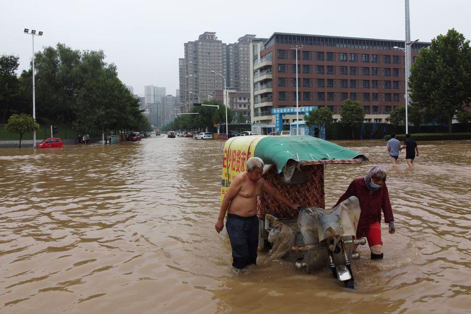 Máy xúc được sử dụng để giải cứu những người mắc kẹt trong lũ lụt ở Trung Quốc - Ảnh 2.