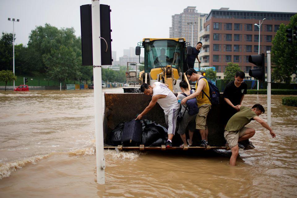 Máy xúc được sử dụng để giải cứu những người mắc kẹt trong lũ lụt ở Trung Quốc - Ảnh 1.
