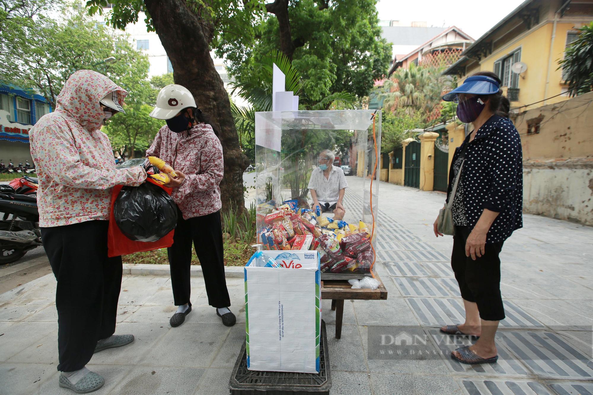 Ấm lòng tủ mì tôm, nước lọc miễn phí cho người khó khăn bên hè phố Hà Nội - Ảnh 2.