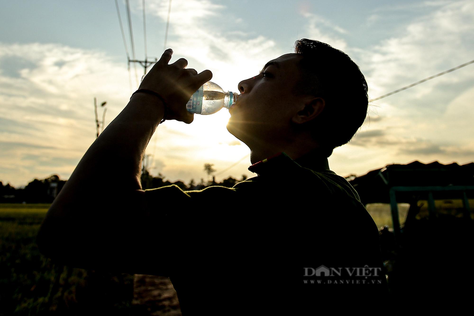Hình ảnh chiến sĩ công an lội ruộng, ăn cơm vội để thu hoạch lúa giúp 141 hộ ở vùng cách ly y tế - Ảnh 9.