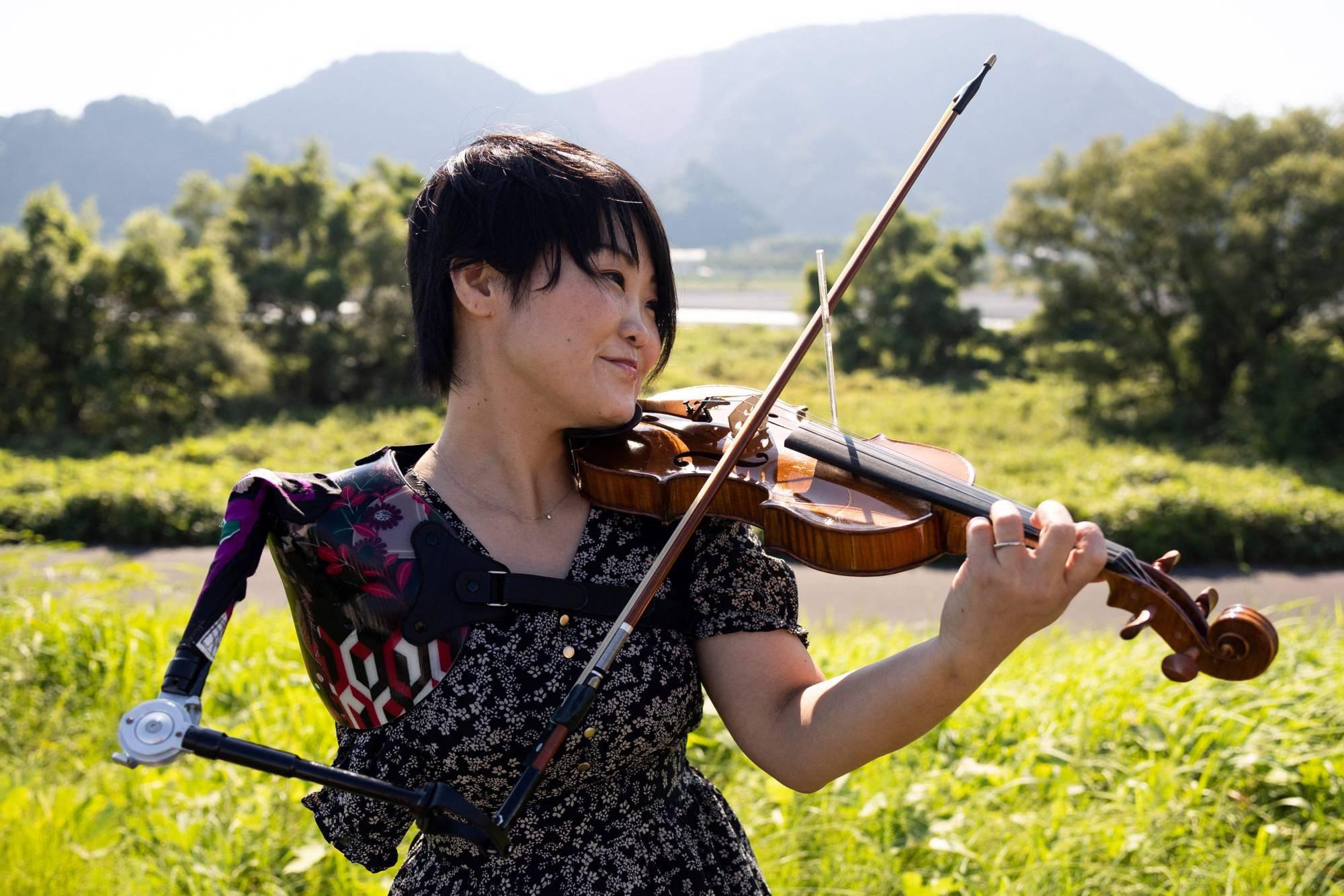 Người phụ nữ mất một cánh tay trở thành y tá, vận động viên, nghệ sĩ violin - Ảnh 1.