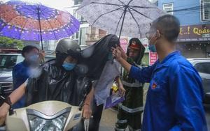 Thi vào lớp 10: Mưa như trút, tình nguyện viên đội mưa che ô, cõng sĩ tử vào phòng thi