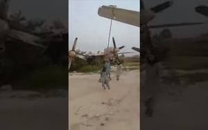 """Clip: Binh sĩ Taliban thích thú """"chế"""" cánh máy bay Mỹ thành xích đu"""