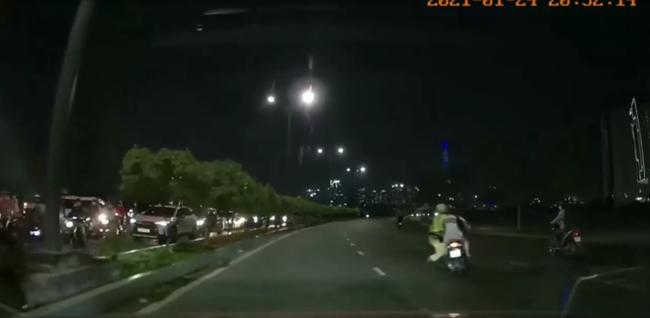 VIDEO: Đu theo xe máy của đôi nam nữ, CSGT ở TP.HCM té ngã xuống đường - Ảnh 1.