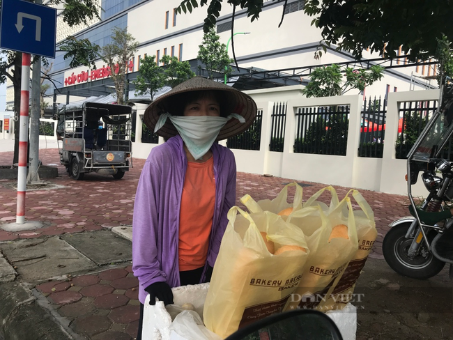 Dù rất lo sợ bị nhiễm Covid-19 nhưng chị Nguyễn Thị Hồng vẫn cố bám trụ bán những túi bánh mì kiếm thêm 2-30 chục nghìn. Ảnh: N.T