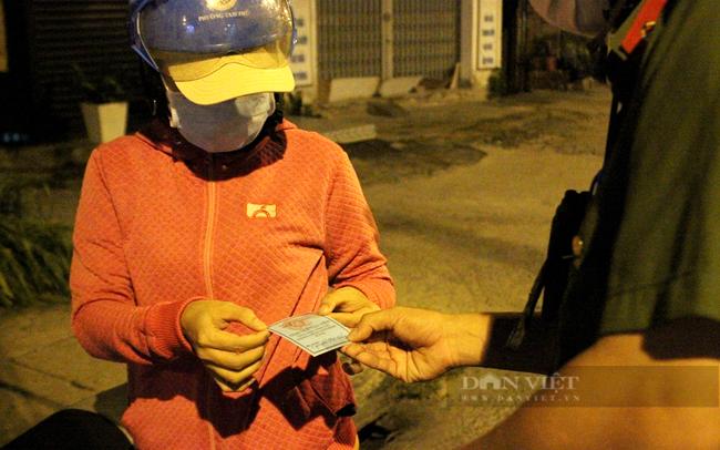 19 giờ, một tình nguyện viên tham gia công tác phòng chống dịch được công an phường Tam Bình kiểm tra giấy giờ và cho phép tiếp tục di chuyển. Ảnh: Nguyên Vỹ
