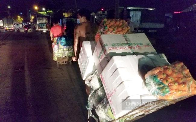 Rau củ được vận chuyển ra bên ngoài chợ, nơi có khách hàng đợi sẵn. (Ảnh: Nguyên Vỹ)