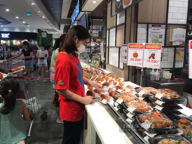 Chị Phạm Thị Trang (La Khê, Hà Đông) cho biết, từ khá lâu rồi chị không được ăn quán vì thế hôm nay đi mua đồ chị mua luôn đồ ăn sẵn vè cho các con. Ảnh: N.T