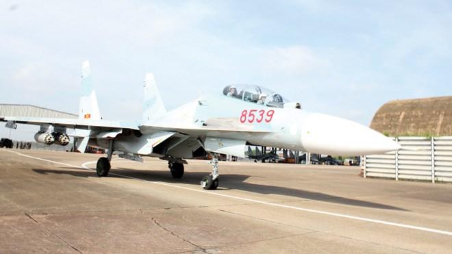 Su 30MK2 với 4 thùng phóng rocket dưới 2 cánh máy bay lăn bánh ra đường băng. Ảnh: Văn Thành
