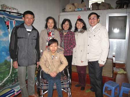 Anh Trần Văn Bình (trái) cùng con gái (ngồi) tiếp nhận quà và xe lăn do các thầy cô  Trường ĐH Quốc gia Hà Nội tặng.