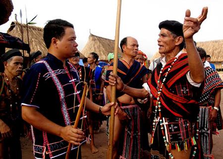Già làng Cơtu Cơlâu Năm(người đội mủ đen bên phải) thôn Pơr ning, xã Lăng, huyện Tây Giang(Quảng Nam) đang tuyên truyền cho lớp trẻ hiểu thêm về tục thách cưới của người Cơtu.