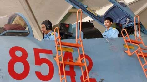 Thiếu tá Nguyễn Công Tênh (ngồi trước) và trung úy Trần Gia Chuân kiểm tra thiết bị trên máy bay Su-30MK2.