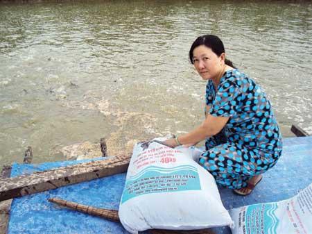 Chị Nguyễn Thị Kim Loan bên bè cá giống.