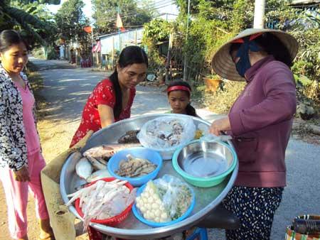 """Nhiều người vẫn vô tư mua thịt gia cầm ở các """"chợ lưu động"""" trong xã Tân Long."""