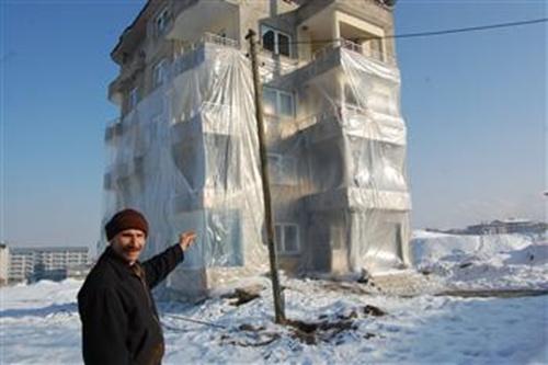 Ông Huseyin Arme đứng trước tòa nhà đã được bọc nylon ba tầng. Ảnh: DHA