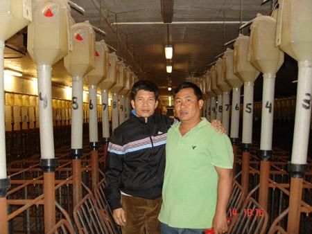 Ông Nguyễn Trí Công (trái) bên trong trại heo CPIG (Canada).