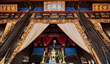 """Gian trung tâm của nhà giữa treo tấm hoành phi lớn viết chữ Hán """"Phạm Phủ Đường,"""" tức nhà của họ Phạm. Hai bên gian giữa là các bàn thờ gia tiên của gia đình ông Cai Cường."""