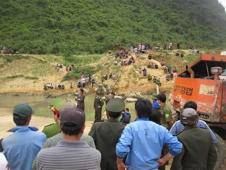 Hàng trăm người đứng xem xe cẩu trục vớt gỗ.
