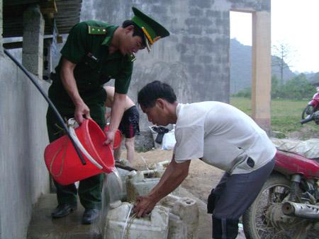 Trung úy Trần Văn Phát múc nước từ bể chứa của công trình nước sinh hoạt  cho người dân xóm Giảng Gà.