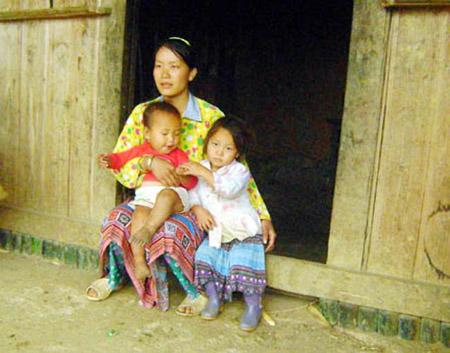 Ba mẹ con chị Giàng Thị Dính trước căn nhà lụp xụp.