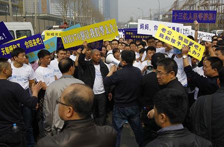 """Những người phản đối cầm biểu ngữ """"Hãy trả lại người thân cho chúng tôi""""; đám đống hét lớn """"Hãy giải thích chuyện đã xảy ra với chiếc máy bay"""". Một vài cá nhân trong đám đông đã ném những lọ nước vào hàng rào lực lượng cảnh sát trước đại sứ quán."""
