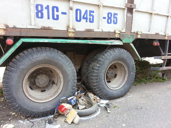 Chiếc xe máy hiệu Future bị cuốn vào gầm xe tải, nát bét.