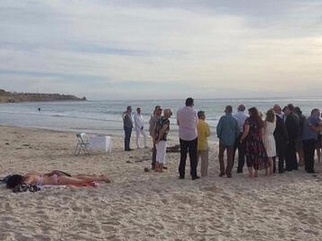 Cô gái bán khỏa thân phơi nắng mặc kệ đám cưới trên bãi biển